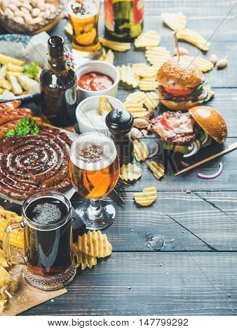 Beer and snack set. Octoberfest food frame concept. Beers assortment, grilled sausages, burgers, fried potato, corn, chips and sauces on dark wooden scorched background. Selective focus, copy space