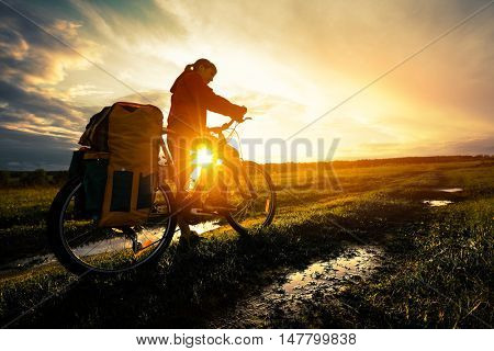 Young lady hiker with loaded bicycle standing on a wet rural road in the meadow at sunset