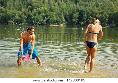 Happy couple spraying water to each other and having fun in summer