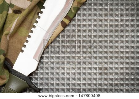 Combat knife on military camouflage fabric and metal background concept