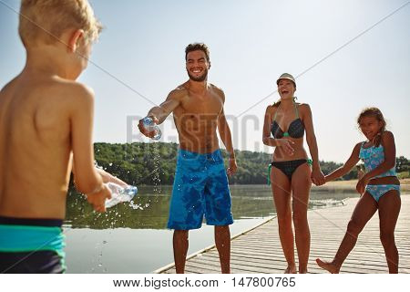Father amd son spray wach other with water in summer