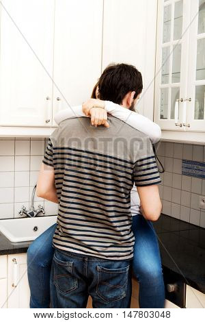 Romantic couple hugging in the kitchen.