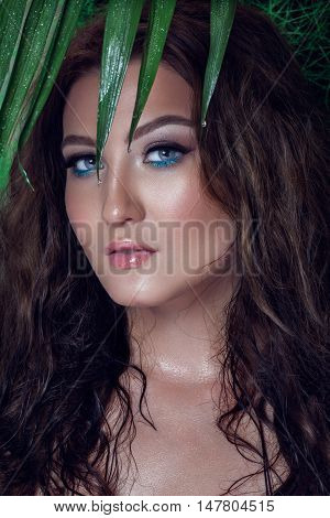 Beautiful sexy woman portrait with wet skin among tropical plants. Beauty, fashion. Spa, healthcare. Tropical vacation.