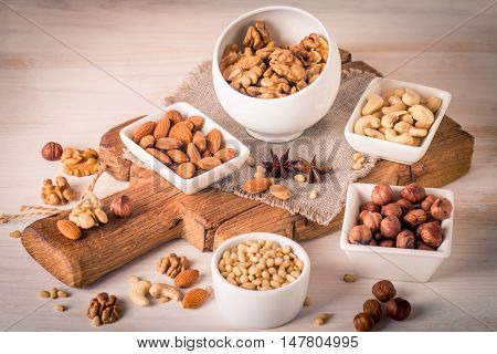 Variety of nuts: almonds, walnuts, hazelnuts cashews and pine nuts in wooden bowls on white wooden background