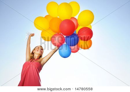Woman holding balloons against sun and sky