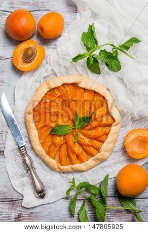 Homemade apricot galette made with fresh organic apricotes on wooden table, top view
