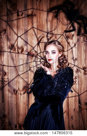 Portrait of a beautiful witch lady in black dress over wooden background. Halloween.