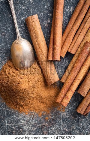 Cinnamon sticks and ground cinnamon on kitchen table. Top view.
