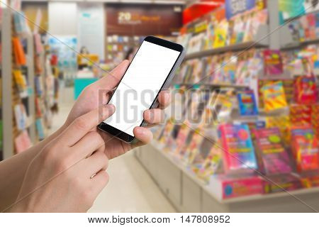 human hand hold and touch blank screen smart phone tablet cellphone on blurry bookshelf in bookstore Online shopping book Concept.