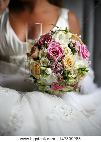 The bride holds a wedding bouquet from roses