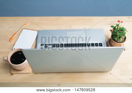 Office desk with laptop Note paper Euphorbia milii flower on terracotta flower pot and coffee. Selected focus on keyboard.