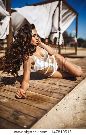 Portrait of attractive sensual woman in bikini with long wavy hair in wind with eyes closed posing on wooden path on beach with tents on background.