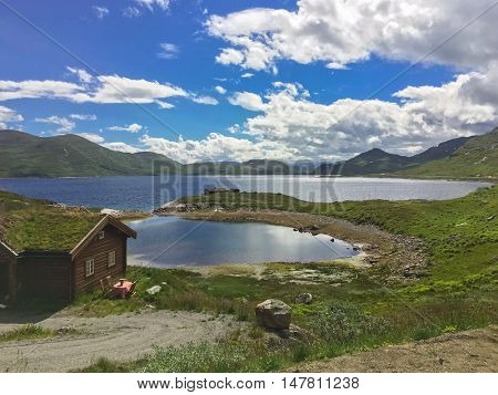 Traditional Norwegian house with grass roof near mountain lake.