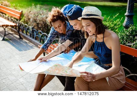 Friends travelers smiling, looking route at map, sitting on bench in park.