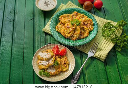 Vegetable pancakes made from zucchini and potato on wooden background