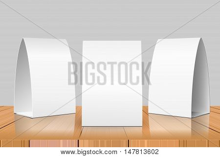 Blank Table Tent isolated on wooden background. Paper vertical cards on wooden table with reflections. Front, left and right view. Vector illustration.