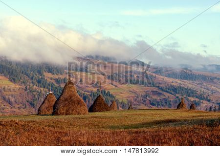 Amazing rural scene on autumn valley. Wooden fence and haystack on a foreground. Carpathians, Ukraine, Europe.
