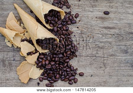 Sugar cones with coffee beans scattered on a wooden rustic background