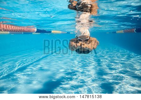 Front view of a girl who swims underwater in the swim pool outdoors. She wears a gray swimsuit with patterns, white swim cap and swim glasses. Sunlight falls from above. Splashes are around her head.