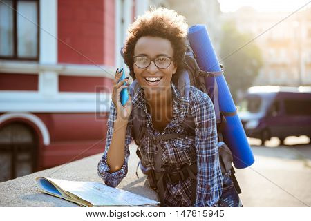 Young beautiful african female traveler with backpack speaking on phone, smiling.