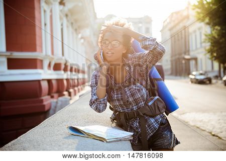 Young beautiful african female traveler with backpack speaking on phone at street.
