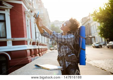 Young beautiful african female traveler with backpack smiling, making selfie at street.