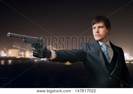 Secret Agent Or Spy Is Aiming With Pistol At Night.