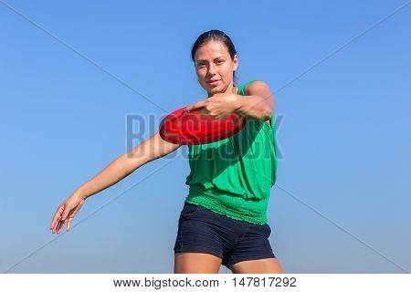 european woman throwing red disc in blue cloudless sky