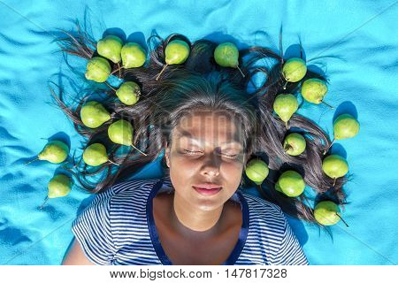 Young woman lying on blanket eyes closed green pears in black hair