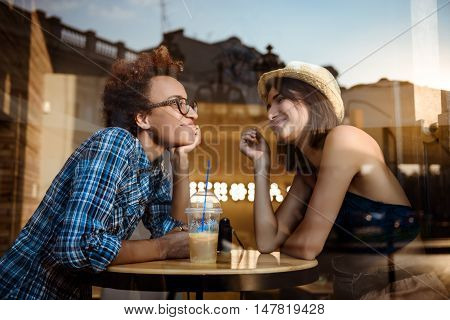 Two young beautiful girls smiling, speaking, resting, sitting in cafe