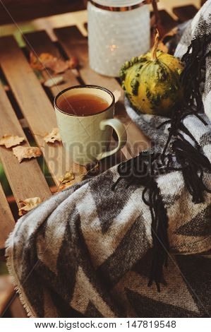 cozy autumn morning at country house cup of tea and warm blanket on wooden table. Still life details