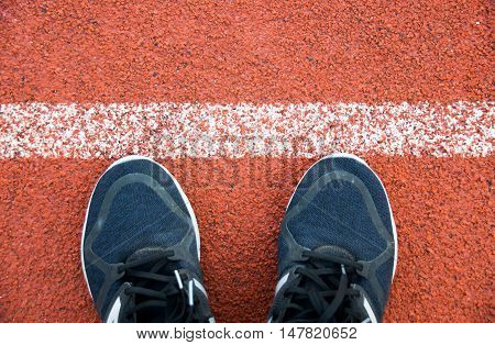 Close Up Running Shoes On Running Track White Lines At Sport Stadium