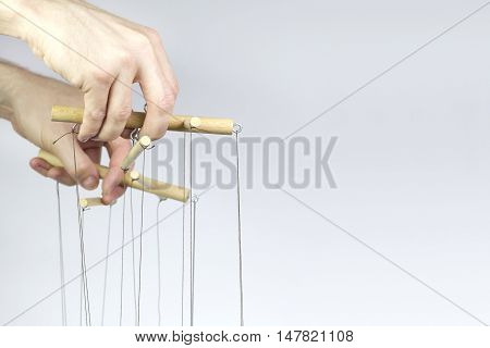 Two hands managing the threads of a puppet.