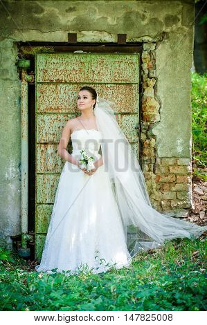 beautiful girl in wedding dress near old door a pensive young bride in the forest