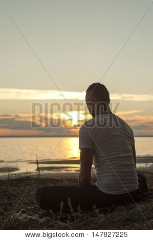 Silhouette of young man sitting on beach on yoga meditation pose