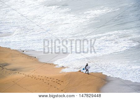 surfer man on the beach with white water wave in the sea at Bells beach Torquay Australia