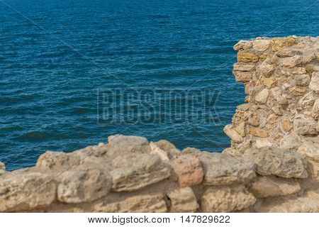 Old Fortress In The Rocks Above The Sea. Rocky Cliff In The Ancient  At The Top. Stone Boulders Stic