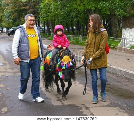 Moscow Russia - September 18 2016: Unidentified family with little girl riding pony horse in autumn park fair
