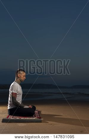 Young Man with tattoos meditating on the beach at sunset. Yoga meditation lotus pose.