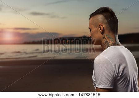 Portrait of young tattoo man meditating on the beach at sunset. Yoga Meditation Pose.