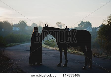 Silhouette of a girl in a raincoat kissing a horse on dark background with blue mist. Rider and horse backlit stand at full height on the road at dawn.