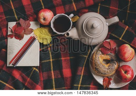 Top view of cozy autumn morning at home. Breakfast with pot of tea and bagel with apples on woolen plaid blanket. Notebook with color pencils