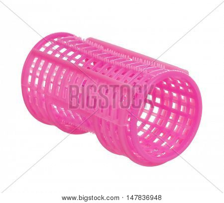 One pink plastic curler isolated on white background. Women tools for creating a beautiful hairstyle from ringlets.