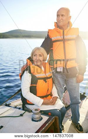 Retired couple in life-vests yachting at leisure