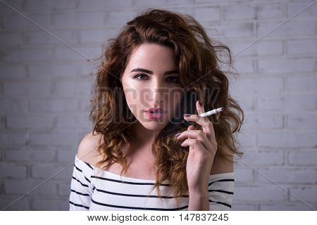 Beautiful Woman Smoking Over White Brick Wall