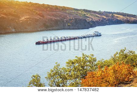 Barge, transporting sand, floating down the river with rocky banks, autumn, sunset