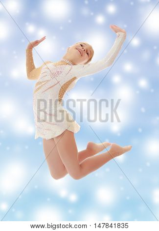 Beautiful little girl gymnast dressed in sports swimsuit, jumps high.On a blue background with large, white, Christmas or new year's snowflakes.