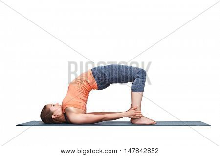 Beautiful sporty fit yogini woman practices yoga asana setu bandhasana - bridge pose advanced variation in studio isolated on white