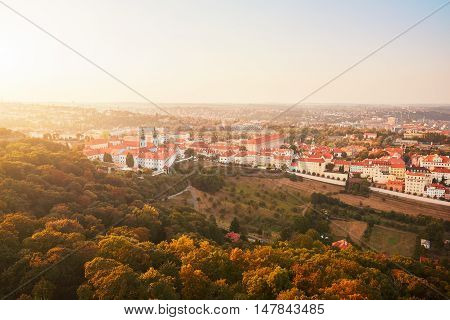 Skyline of historical part of Prague Capital. Strahov Monastery and park under Petrin hill at the amazing sunset.