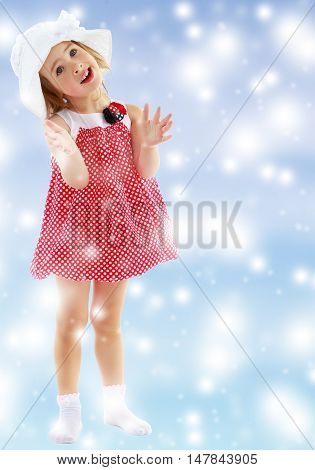 Joyful little girl in a very short polka dot dress and white Panama city beach , claps.Full growth.Gentle blue Christmas background with white snowflakes abstract.